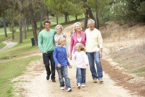 Three-generation family enjoying walk in park.