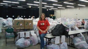 Volunteer sitting by donations