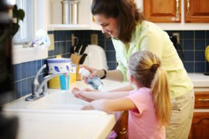 mother helping daughter wash hands.