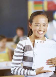 Portrait of cheerful girl holding book while classmates in background