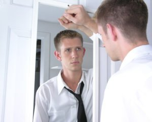 man thinks into the mirror