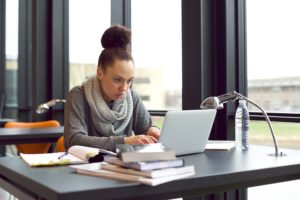 Young African american girl sitting in library searching information on laptop for her assignment. Young woman sitting at table surfing internet for notes for her study.