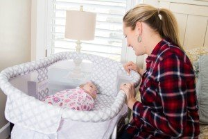 Mother looking at baby in bassinet