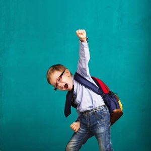 smiling little boy with big backpack jumping and having fun
