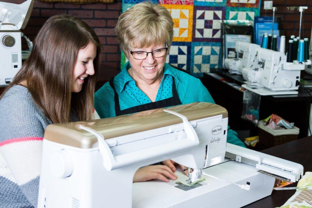 Woman teaching girl to sew